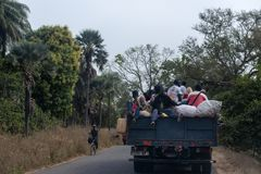 Eople traveling in the back of a truck in Cacheu Region, in Guinea Bissau. Cacheu, Republic of Guinea-Bissau - February 1, 2018: People traveling in the back of royalty free stock photo