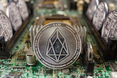 EOS coin on a technology circuit. EOS coinclose-up on a computer circuit motherboard as a blockchain technology payment network. Digital cryptocurrency concept royalty free stock photo