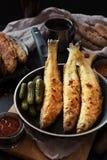 Eperlano frito en una cacerola oscura con la salsa Foto de archivo libre de regalías