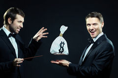 Ephemeral money. Man in tuxedo taking sack of money out of hands of other men with a wand Royalty Free Stock Photo