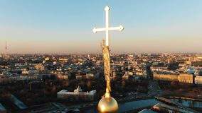 Aerial flying around an angel on spire of Peter and Paul Fortress at sunset, close-up. Historical panorama of St. Epic aerial flight around angel on spire of stock video