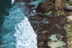 Aerial view of blue ocean waves crashing into rocky coast. Epic aerial view of blue ocean waves crashing into rocky coast stock image