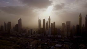 Epic aerial view of the urban landscape, with large skyscrapers and the sun breaking through the clouds. Dubai, UAE. Sun rays from behind the clouds illuminating stock footage