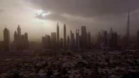 Epic aerial view of the urban landscape, with large skyscrapers and the sun breaking through the clouds. Dubai, UAE stock footage