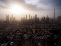 Epic aerial view of the urban landscape, with large skyscrapers and the sun breaking through the clouds. Dubai, UAE. Sun rays from behind the clouds illuminating Royalty Free Stock Image