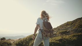 Nomad hipster millennial backpacker tourist. Epic amazing shot of camera following adventure hike walk of young traveler tourist exploring mountain top. Young stock footage