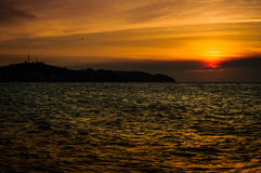 Epic Autumn Island Sunset. Sunset over the sea in autumn season with epic clouds on the sky with sun that looks like a fiery ball Stock Photo