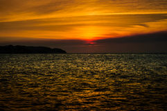 Epic Autumn Island Sunset. Sunset over the sea in autumn season with epic clouds on the sky with sun that looks like a fiery ball Stock Images