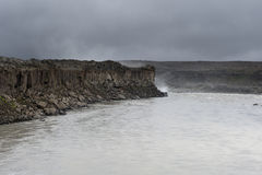 Epic basalt columns cliff near the dead river on a dark and clou Stock Photo