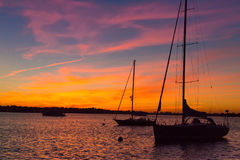 Epic and beautiful sunset over harbor with sailboat silouettes Royalty Free Stock Image