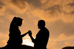 Epic cinematic portrait of young couple in love looking at each other at sunset with woman pregnant holding hands. Portrait of young couple in love looking at royalty free stock images