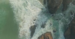 Epic Cliff and Ocean Waves Top View. Beautiful aerial or drone shot along the coast of Portugal on a sunny day. Epic cliffs and ocean waves birds eye view during stock video