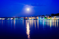 Epic Full Moon Night Scenery. Epic natural environment with full moon in the sky and reflection of its light and city lights on the surface of the sea Stock Images