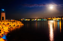 Epic Full Moon Night Scenery. Epic natural environment with full moon in the sky and reflection of its light and city lights on the surface of the sea Royalty Free Stock Photos