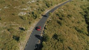 Traveling in convertible car for life. Epic and inspiring aerial drone footage of two best friends or couple drive on empty picturesque mountain road during stock video footage