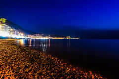 Epic Island Night Scenery. Epic and poetic scenery of an island in the night with building lights reflecting from the surface of the sea Stock Photo