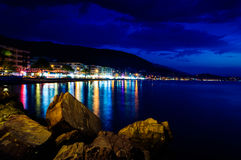 Epic Island Night Scenery. Epic and poetic scenery of an island in the night with building lights reflecting from the surface of the sea Royalty Free Stock Photos