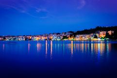 Epic Island Night Scenery. Epic and poetic scenery of an island in the night with building lights reflecting from the surface of the sea Stock Photos