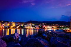 Epic Island Night Scenery. Epic and poetic scenery of an island in the night with building lights reflecting from the surface of the sea Stock Images