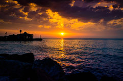 Epic Island Sunset Scenery. Epic and poetic scenery on an island in the sunset with majestic clouds and sun lights reflecting from the surface of the sea with Royalty Free Stock Images