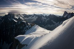 Epic landscape with line of mountaineers on decent from Aiguille du Midi cable car station stock image