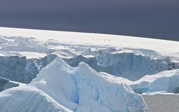 Epic scale. Four hikers scale a snow-covered incline in Antarctica Stock Photography
