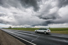 Epic sky, fast moving car on the road. Stormic weather, massive sky and summer field Royalty Free Stock Photography