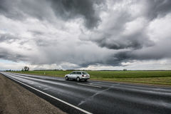 Epic sky, fast moving car on the road. Stormic weather, massive sky and summer field Stock Images