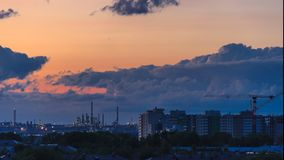 Epic storm clouds at sunset over city skyline 4K timelapse. Epic storm clouds moving fast at sunset over city skyline 4K time lapse. Oil refinery lights, power stock footage