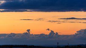 Epic storm clouds at sunset over city skyline 4K timelapse. Epic storm clouds moving fast at sunset over city skyline 4K time lapse. A stadium floodlights,mess stock video footage