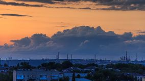 Epic storm clouds at sunset over city skyline 4K timelapse. Epic storm clouds moving fast at sunset over city skyline 4K time lapse. Oil refinery lights, power stock video footage