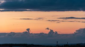 Epic storm clouds at sunset over city skyline 4K timelapse. Epic storm clouds moving fast at sunset over city skyline 4K time lapse. A stadium floodlights,mess stock footage