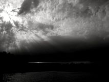 Epic sunrays in monochrome. Sunrays over a lake in monochrome, piking through clouds Royalty Free Stock Images