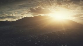 Epic sunrise flare mountain village aerial view stock video footage