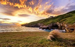 An epic sunset with dramatic burning clouds in Tunnel Beach of Dunedin, New Zealand stock photography