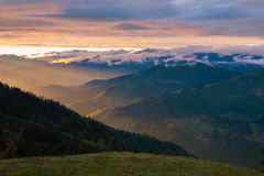 Epic sunset in the mountains after storm. Rays of setting sun illuminate the slopes of the ridges and the clouds floating above them. Vintage image Royalty Free Stock Image