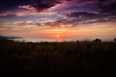Epic Sunset Over The Sea With Natural Landscape. Epic sunset with majestic clouds on a natural landscape surrounded with trees under the summer sky and open Stock Photos