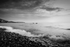 Epic Sunset Seashore. Epic and cinematic sunset seashore environment in black and white with majestic clouds on the sky and mist on the horizon Royalty Free Stock Photography