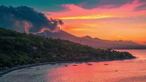 Epic sunset timelapse in the Jemeluk bay with a view of the ocean and clouds above the volcano Agung in Bali in stock video