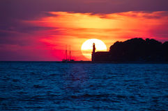 Epic sunset view with lighthouse and saiboat Royalty Free Stock Image