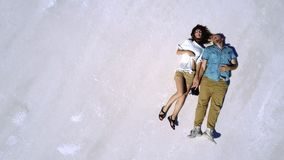Epic top view cinematic aerial shot of relaxed happy couple lying together in the middle of Bonneville salt lake desert. stock video