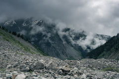 Epic view of the moraine in a mountain gorge. Next to the glacier the Chalaadi. Foggy day in the mountains. Svaneti, Georgia, Caucasus Royalty Free Stock Photo