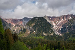 Epic view of the rocky mountain range after the storm. Heavy clouds float above a gray, rocky wall that is lit by the rays of the sun Stock Image