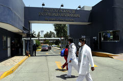 Epicenter of influenza epidemic. Hospital workers walk past the main entrance of the Mexican Institute of Respiratory Illnesses (INER) on April 28, 2009 in Royalty Free Stock Photography