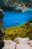 Epicki widok błękit zatoka Assos wioska Kefalonia od fortecy above Biały jacht przy kotwicą w spokojny piękny barwionym obrazy royalty free