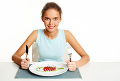 Epicure. Portrait of pretty young girl with fork and knife in hands and plate with gourmet coarse in front Stock Photo