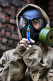 Epidemic. HDR. Person in gas mask with syringe Stock Photo