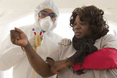 Epidemic desease research. Doctor in protective suit is drawing blood from african woman  to perform a test Stock Image