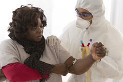 Epidemic desease research. Doctor in protective suit is drawing blood from african woman  to perform a test Stock Photo
