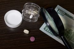 The epidemic of drugs. The tablets are in a clear plastic container with the lid removed. Several tablets lie on the table. There. Is a money bill and a Stock Photos